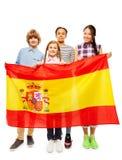 Cuatro niños adolescentes multiétnicos que sostienen la bandera española Imagen de archivo libre de regalías