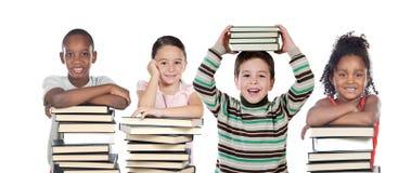 Cuatro niños con muchos libros Fotografía de archivo libre de regalías