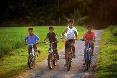 Cuatro niños con sus bicicletas Imágenes de archivo libres de regalías
