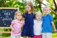Cuatro niños emocionados por una pizarra Fotos de archivo libres de regalías