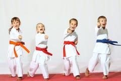 Cuatro niños en kimono golpearon un sacador en un fondo blanco foto de archivo libre de regalías