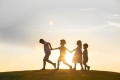 Cuatro niños están jugando en puesta del sol Foto de archivo libre de regalías