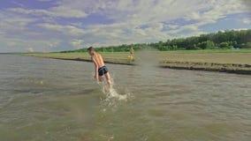Cuatro niños están salpicando en el agua