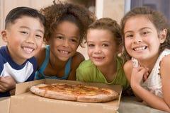 Cuatro niños jovenes dentro con la sonrisa de la pizza Fotografía de archivo libre de regalías