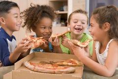 Cuatro niños jovenes dentro que comen la pizza Foto de archivo