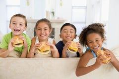 Cuatro niños jovenes que comen los cheeseburgers Fotos de archivo