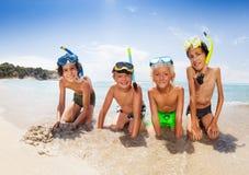 Cuatro niños juegan en las máscaras del equipo de submarinismo de la playa que llevan Fotos de archivo libres de regalías