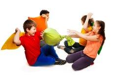Cuatro niños que tienen lucha de almohada Foto de archivo