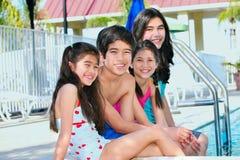 Cuatro niños por el lado de la piscina Fotos de archivo
