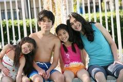 Cuatro niños por la cara de la piscina Imagen de archivo libre de regalías