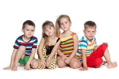Cuatro niños preescolares se sientan en el piso Fotografía de archivo