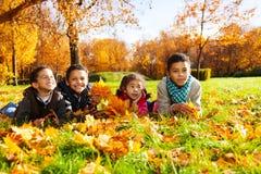 Cuatro niños puestos en hojas de otoño Imagen de archivo libre de regalías