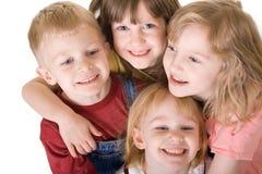 Cuatro niños que abrazan de arriba foto de archivo