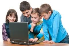 Cuatro niños que estudian usando una computadora portátil Fotografía de archivo libre de regalías