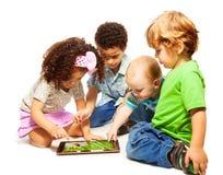 Cuatro niños que juegan la tablilla Imagen de archivo