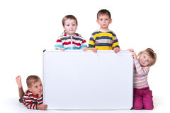 Cuatro niños que llevan a cabo a una tarjeta blanca Imagen de archivo libre de regalías