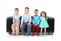 Cuatro niños que se sientan en el sofá de cuero negro Foto de archivo libre de regalías
