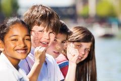 Cuatro niños sonrientes que pasan días de fiesta al aire libre Imágenes de archivo libres de regalías