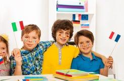 Cuatro niños con las banderas en las mejillas que agitan banderas Foto de archivo libre de regalías