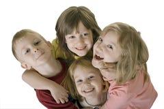 Cuatro niños que abrazan de arriba Fotos de archivo libres de regalías