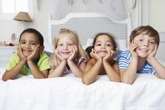 Cuatro niños que juegan en cama junto Foto de archivo