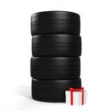 Cuatro nuevos neumáticos de coche y regalo blanco con la cinta roja en el blanco Foto de archivo libre de regalías