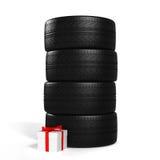 Cuatro nuevos neumáticos de coche y regalo blanco con la cinta roja en el blanco Fotografía de archivo