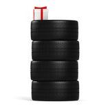 Cuatro nuevos neumáticos de coche y regalo blanco con la cinta roja en el blanco Fotos de archivo