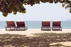 Cuatro ociosos en una playa abandonada con vistas al horizonte Imagen de archivo
