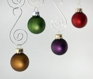 Cuatro ornamentos que cuelgan contra blanco Imagen de archivo libre de regalías