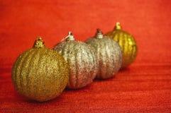 Cuatro oro y la Navidad de la plata juegan en un primer rojo del fondo Año Nuevo, fondo de la Navidad Fotografía de archivo