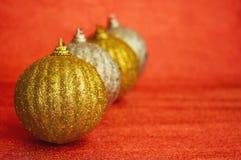 Cuatro oro y la Navidad de la plata juegan en un primer rojo del fondo Año Nuevo, fondo de la Navidad Imagenes de archivo