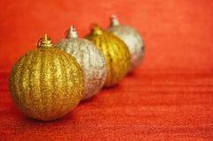 Cuatro oro y la Navidad de la plata juegan en un primer rojo del fondo Año Nuevo, fondo de la Navidad Fotos de archivo libres de regalías