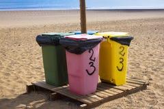 Cuatro papeleras de reciclaje para diversa basura Papel, vidrio, comida, plástico Playa, arena Imágenes de archivo libres de regalías