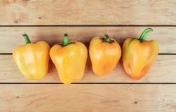 Cuatro paprikas amarillos en la tabla Foto de archivo libre de regalías