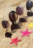 Cuatro pares de gafas de sol en la playa Fotos de archivo libres de regalías