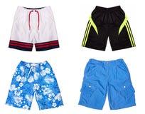 Cuatro pares de pantalones cortos coloreados aislados en el fondo blanco, collage de pantalones cortos Imagenes de archivo