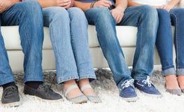 Cuatro pares de pies al lado de uno otros contra el sofá Fotografía de archivo