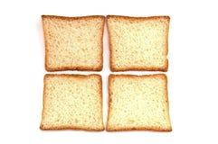Cuatro pedazos de pan de la tostada están en un fondo blanco fotos de archivo
