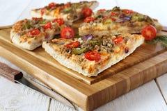 Cuatro pedazos de pizza sabrosa con los tomates, las salmueras y el mea picadito Fotografía de archivo libre de regalías