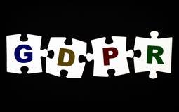 Cuatro pedazos de rompecabezas con las letras GDPR en fondo negro Fotografía de archivo libre de regalías