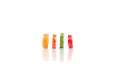 Cuatro pedazos que cortaban de verduras arreglaron en el fondo blanco Foto de archivo
