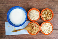 Cuatro pequeños cuencos con los cereales diferentes y el cuenco con la leche, comida sana Imagenes de archivo