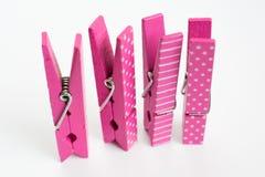 Cuatro pernos de ropa rosados con los modelos de la diversión que se levantan Fron anguloso Imagenes de archivo