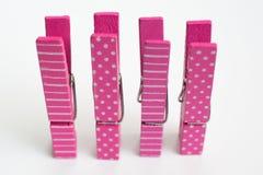 Cuatro pernos de ropa rosados con los modelos de la diversión que se levantan a Front View Foto de archivo libre de regalías