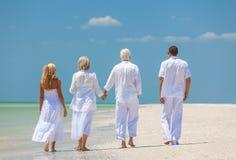 Cuatro personas, dos mayores, pares de la familia, caminando en tropical sean fotografía de archivo