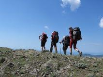 Cuatro personas en backpacking Fotos de archivo libres de regalías