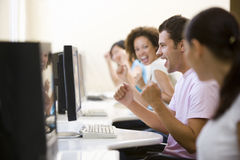 Cuatro personas en sala de ordenadores que animan y que sonríen Foto de archivo