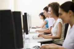 Cuatro personas en sala de ordenadores que pulsan y que sonríen Foto de archivo