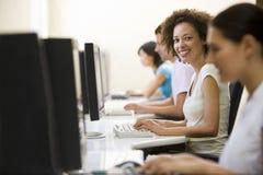 Cuatro personas en sala de ordenadores que pulsan y que sonríen Imagen de archivo